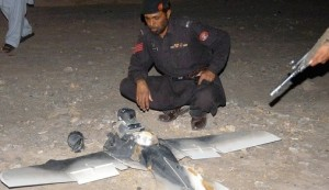 A Pakistani security officer examines a crashed U.S. surveillance drone.