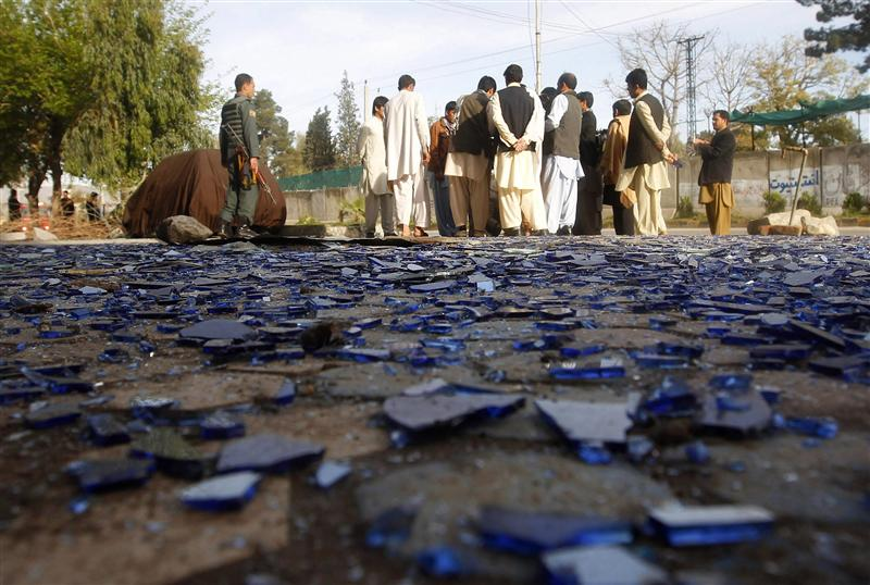 People gather near pieces of broken glass at the site of a suicide attack in Jalalabad