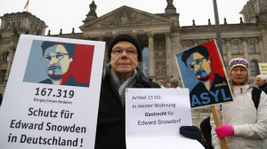 Demonstrator supporting fugitive former U.S. NSA contractor Snowden holds up a banner outside Reichstag in Berlin